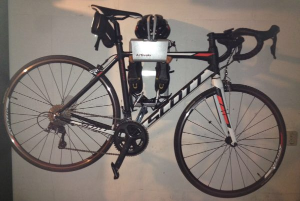 Grey vertical hanging system for racing bike on the wall