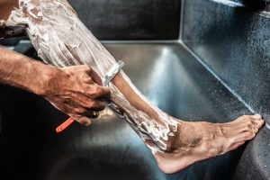 Grooming for cyclists: Cyclist shaves his legs with shaving foam