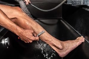 Grooming for cyclists: cyclist shaves his legs without shaving foam
